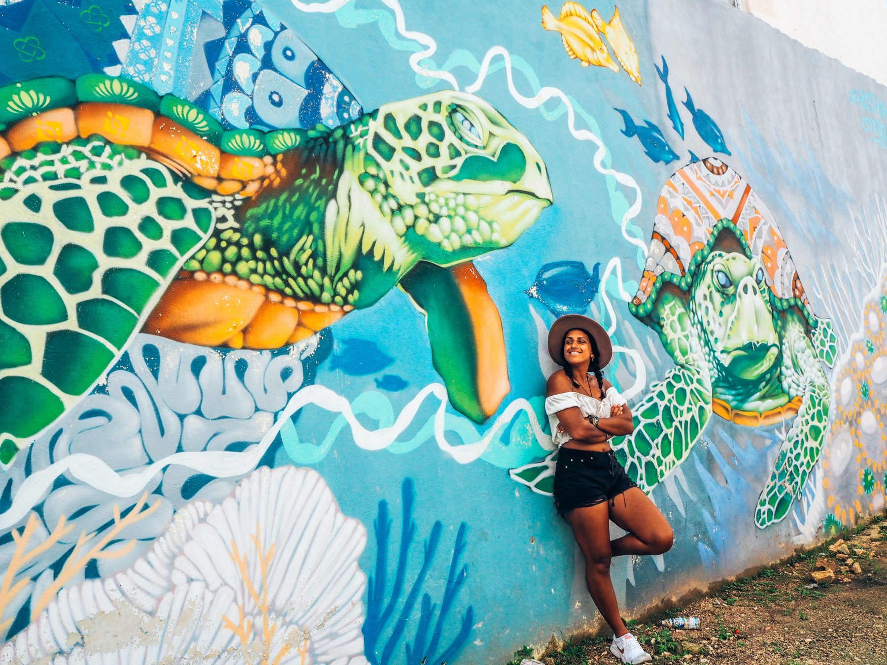 Girl in white top, black shorts and hat leaning against wall with sea turtle street art in mexico