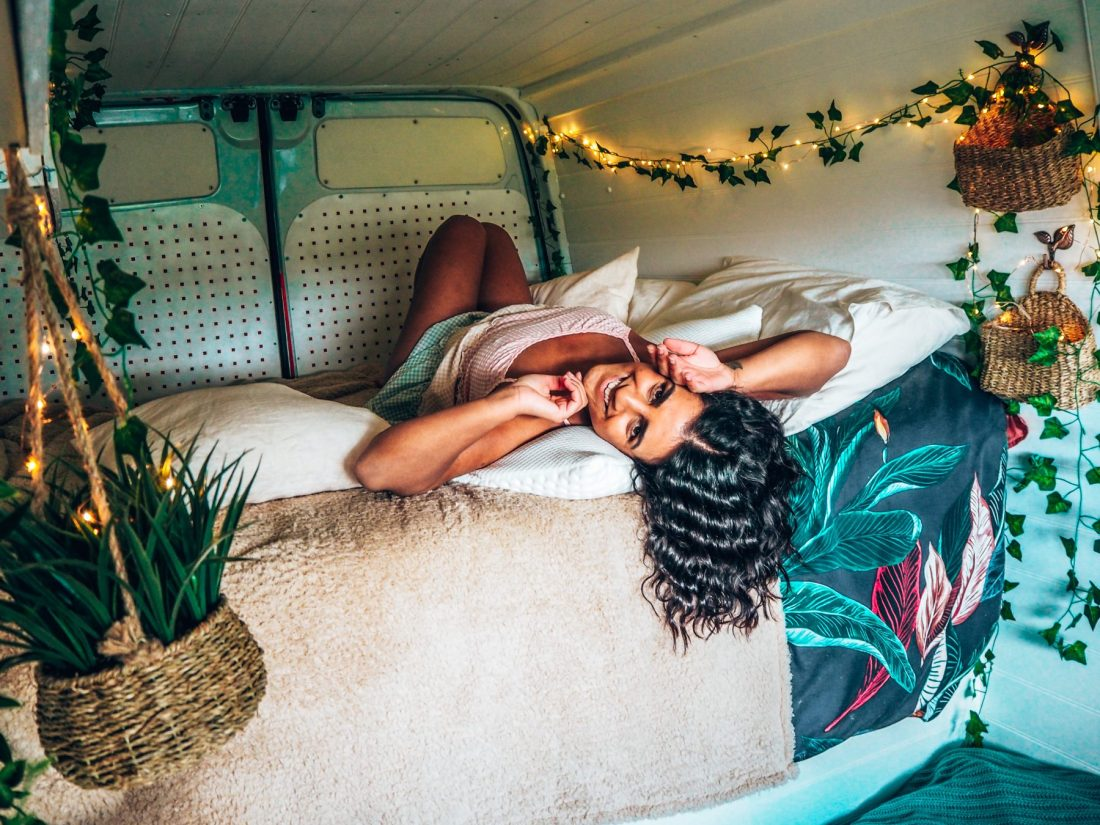 Lucy lays in pastel gingham dress on camper van bed surrounded by fairy lights and on a TEMPUR memory foam pillow. out of this world sleep experiences.