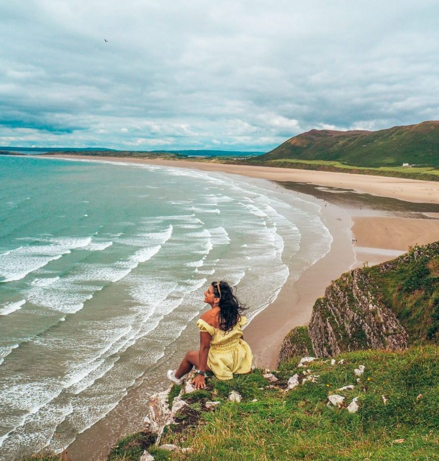 Lucy in yellow dress on cliff overlooking Rhossili Bay, on the Gower Peninsula
