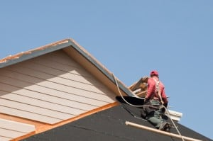 Depositphotos_6183903_s-Roofer-with-Harness-on-top-of-house-300x199