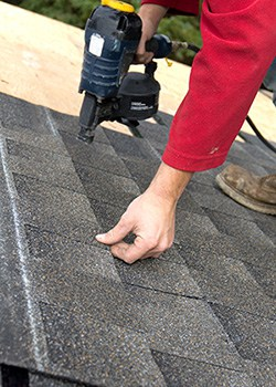 Roofer Nailing Shingles to Roof