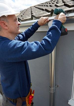 Roofer Repairing Gutter