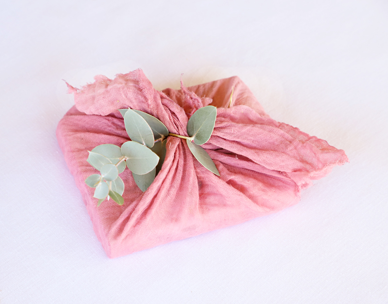 gift wrapped in dyed cheesecloth with eucalyptus