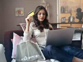 امرأة تحمل بطاقة أثناء تشغيل الكمبيوتر المحمول الفضي
