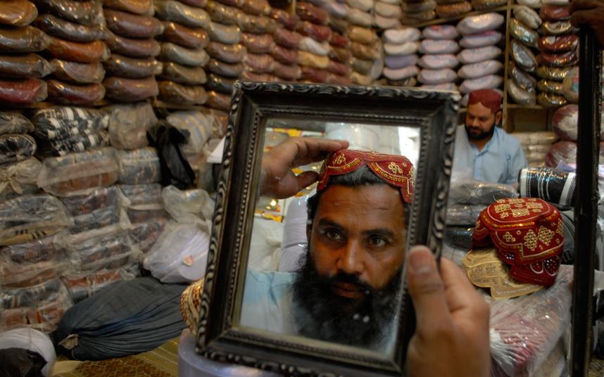 رجل باكستاني يجرب قبعة تقليدية للرأس في متجر وسط بيشاور استعدادا لحلول شهر رمضان المبارك.
