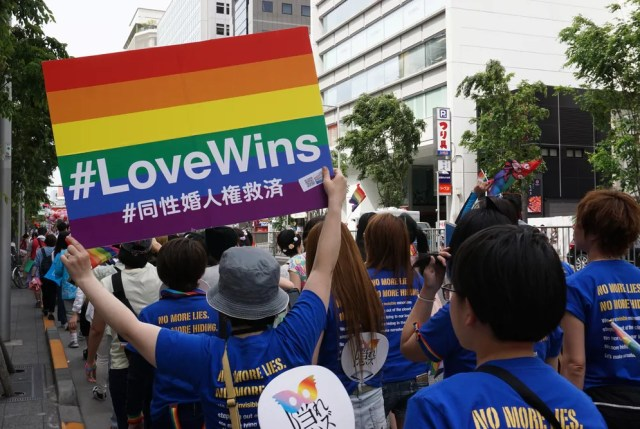 Persona sosteniendo rainbow er Love gana por los derechos del matrimonio entre personas del mismo sexo entre las personas que marchaban en el Tokyo Rainbow Pride (TRP) Parade 2016 en Shibuya, Tokio, Japón.