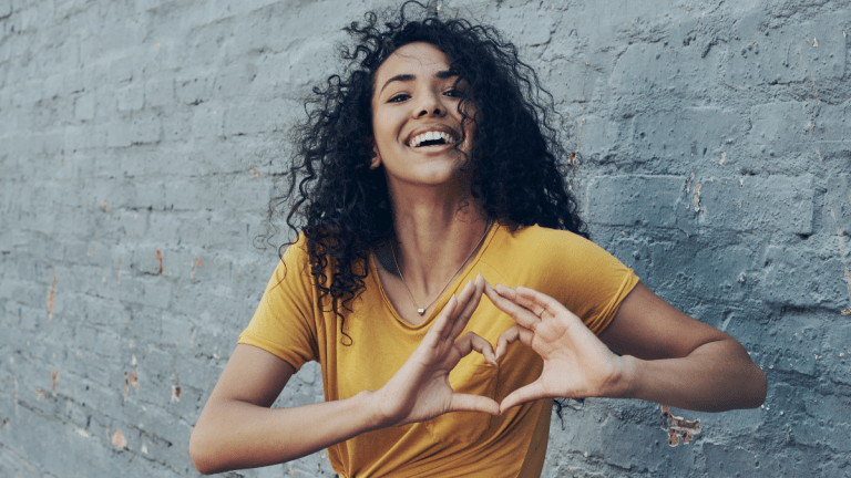 woman making a heart sign with her hand