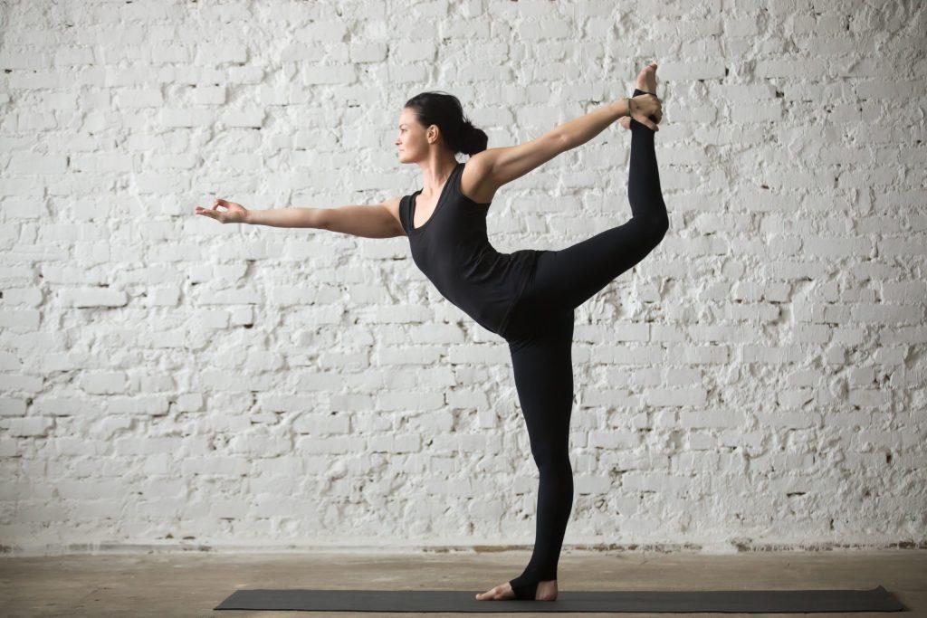 Mujer yogi realizando la postura de Natarajasana