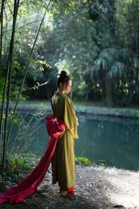 woman in green kimono standing near a river