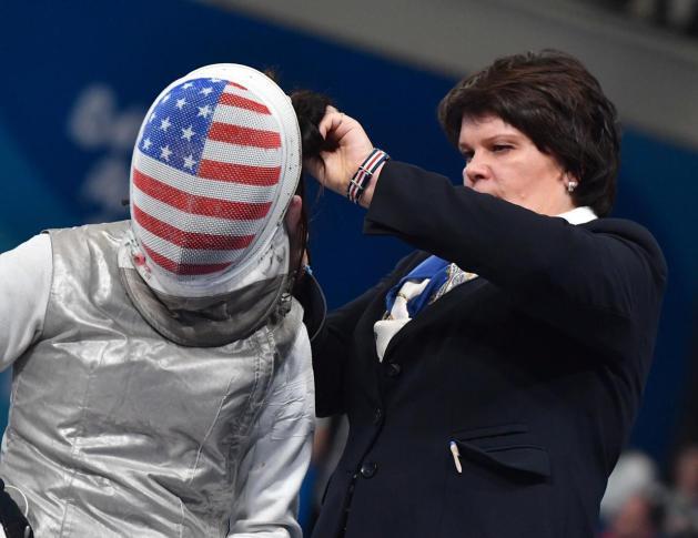 Natalia Zhuravleva fixes hair of American foil fencer Lee Keifer