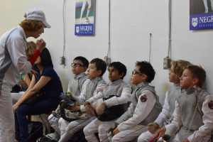 Coach preparing youth fencers to competition