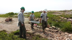 Trail workers at Acadia National Park carry a heavy stone on a gurney for a project on Sargent Mountain