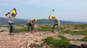 Members of Youth Conservation Corps swing sledge hammers to bust rocks as part of project on Sargent Mountain