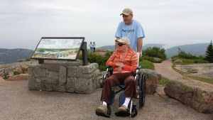 Abraham Hattar and Galyna Moroz, seated in wheel chair, on the Cadillac Mountain summit.
