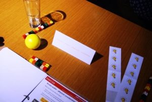Image shows items on a desk at a workshop including a glass of water, a yellow stress ball and a workbook