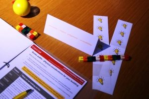 Image shows items on a desk at a workshop, including a yellow stress ball, some kinetic toys and a workbook