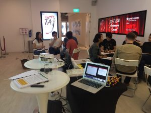 images shows the workshop space in the theatre foyer which is modern and white. Two groups of people seated in circles in discussion.