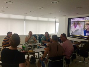 image shows workshop participants sitting around a large table, with a video screen at one of the room showing a video about neurodiversity