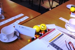 a table top set up with training materials, including an open workbook, cup and saucer, pair of glasses and two bright yellow stress balls with smily faces