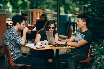 Happy people sitting around a table working-Are you depressed about your job search?