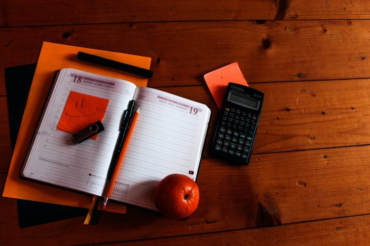 Notebook open on a table with pencil and calculator and apple. The owner is considering a career change due to workplace anxiety needs a career coach in Houston, TX with accessible career. If you need affordable counseling and educational services houston, TX start here for online career coaching services in Texas.