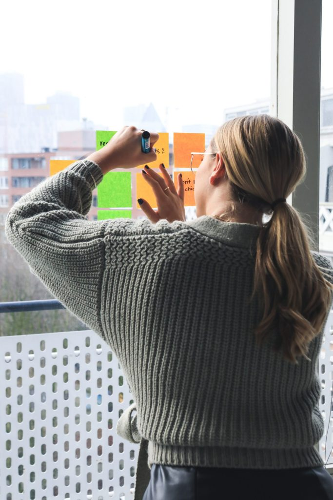 A woman writes on sticky notes on a window. She feels more focused since career planning with a career coach in Houston, TX with Accessible Career. She has noticed that she is feeling less anxiety at work.