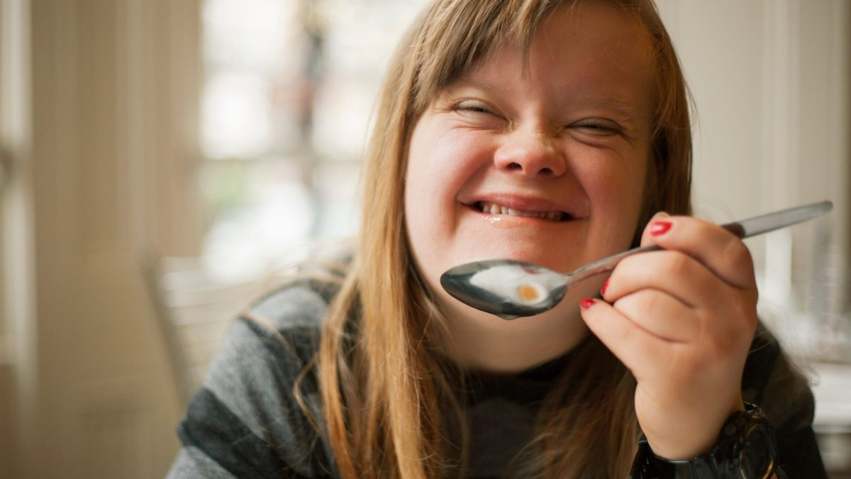 Young woman smiling and holding up spoon