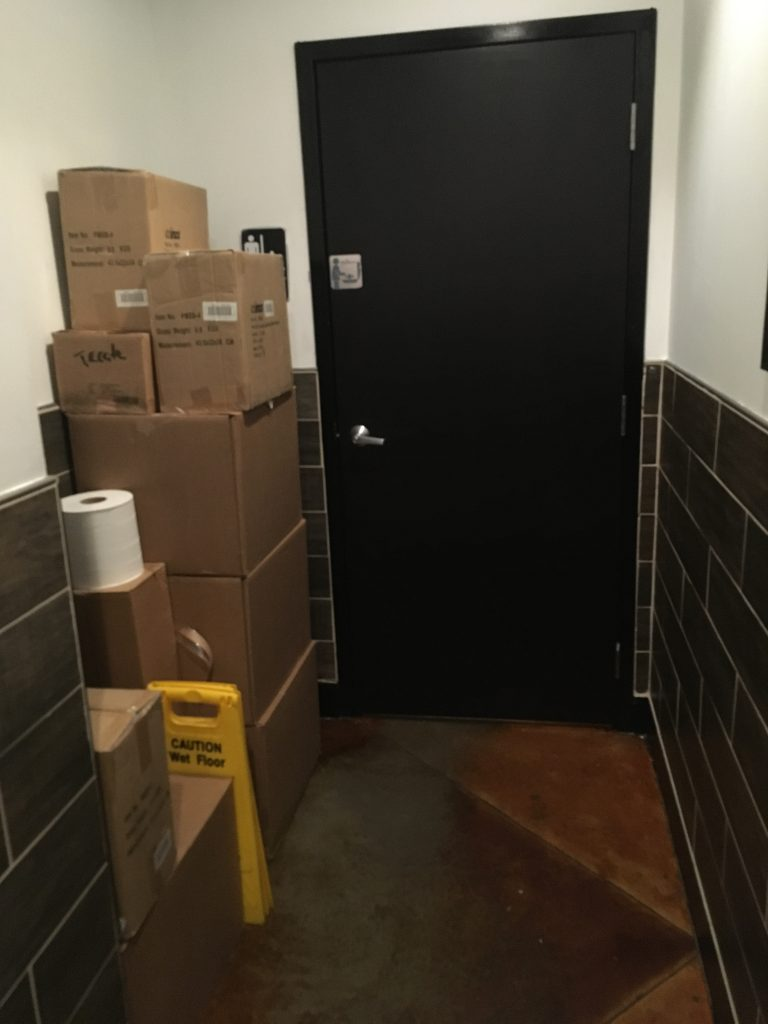 Storage boxes next to a bathroom door prevent a wheelchair user's ability to easily open the door and enter