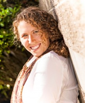 Image Description: The creator of this site, Suzanne Bair, is standing with her back to a light colored wall with green bushes in the background. She has light brown, curly hair, is wearing a white blouse with a dark patterned scarf and is smiling toward the camera.