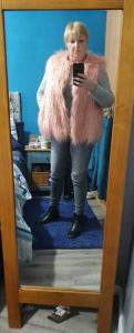 Me in front of a mirror with a pink gillet , jeans and a jumper on