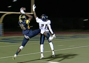 "Inderkum's 6'4"" receiver #15 Tarik Bible grabs a 9-yard pass reception over River City #21 Keith Cole."