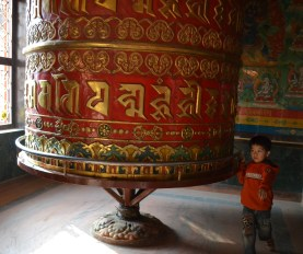 A kid spinning a prayer wheel in Boudhanath Stupa
