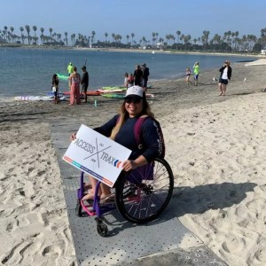 Image shows Channing, a brunette woman, smiling holding an Access Trax sign while in her manual wheelchair on top of grey Access Trax mats on sand at the bay. There is water in the background with people and kayaks.