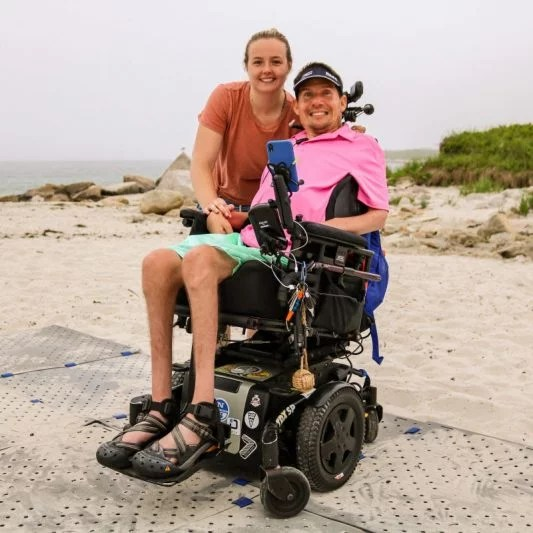 A woman stands to the right of a man smiling, sitting in his power wheelchair while at the beach on a foggy day. They are on a grey beach mat.