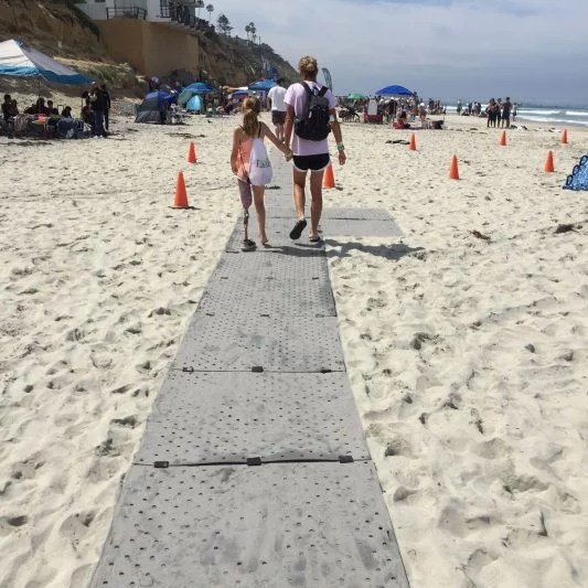 A mom and daughter who has a prosthetic leg are walking down a grey beach path over sand.