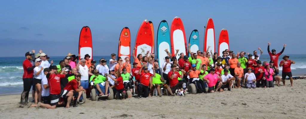A large group of surfers and volunteers pose for a photo on the sand with surf boards upright behind them.