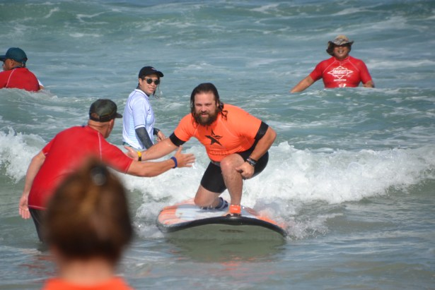 A male surfer with brown hair kneels on the surf board in a small wave to give an instructor a high-give.