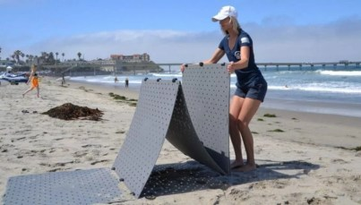 A blonde woman wearing a blue shirt unfolds a grey Beach Trax pathway over sand at the beach.