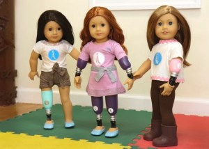 Three American Girl Dolls featuring a combination of prosthetic arms and legs.