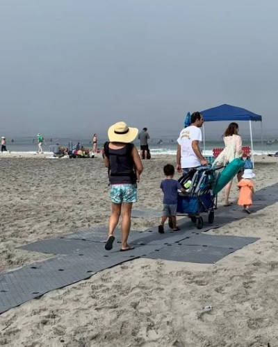 A family at the beach heads to the sea shore atop Access Trax pathway.