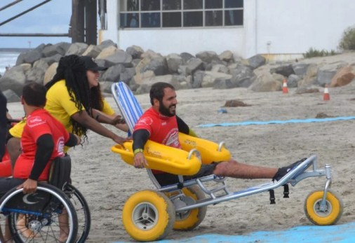 A man sits in long-sitting in a beach wheelchair with large yellow arm rests with two women pushing him at the beach.