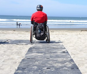 A man wearing a sports helmet sits in his wheelchair looking out at the ocean before going surfing. He is using a wheelchair accessible beach pathway.