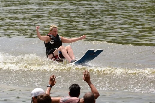 A woman smiles and raises her hands up to balance while sitting in the adaptive water ski on the lake as people cheer her on.