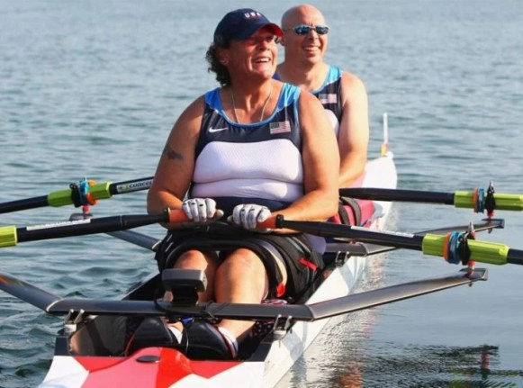 Angela Madsen is pictured smiling while rowing in the front of a 2-person team during the Paralympics.