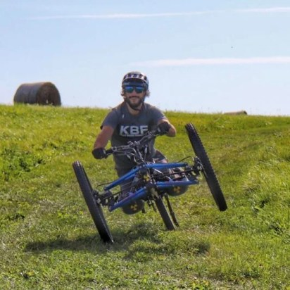 Greg smiles as he rides his off-road handycle down a grassy trail. He is wearing a Kelly Brush Foundation t-shirt and a helmet.