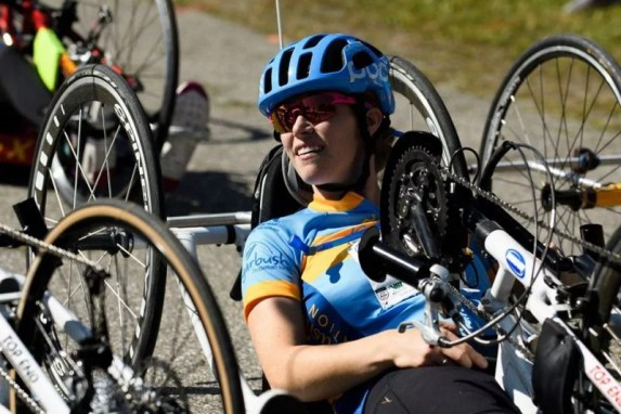 Kelly Brush Foundation Founder Kelly smiles as she pedals her handcycle. She is wearing a blue helmet and sunglasses.