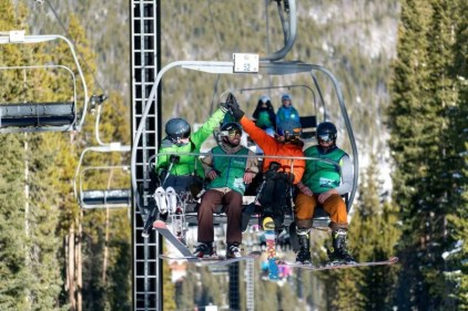 Skiers are shown high-fiving on a ski lift in the mountains.