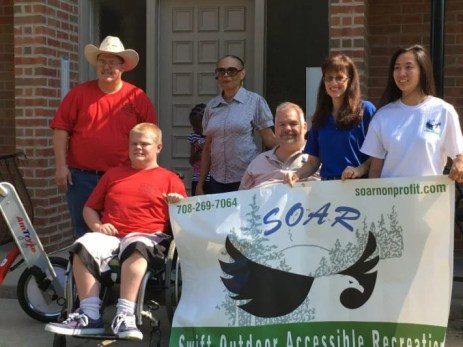 "A group of people smile on a front porch holding a banner that says ""SOAR Swift Outdoor Accessible Recreation."" Two men are in wheelchairs and 4 men and women are standing."