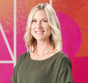 Kelly is a blonde woman with shoulder length hair. She is smiling and wearing an olive green blouse. The background has bright pink and orange colors on the wall.