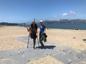 Image shows two women at the beach smiling for a photo while standing on a grey beach pathway. Kelly is wearing a blue shirt and cargo pants and Veneranda is wearing a short sleave camo jumpsuit with a hat. Veneranda uses forearm crutches for mobility. The Golden Gate Bridge is in the bay in the background.